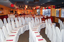 Large social event with white and red chair covers and wedding decorating.