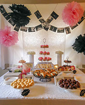 Social party with prepared table of food and flowers with overhanging photos